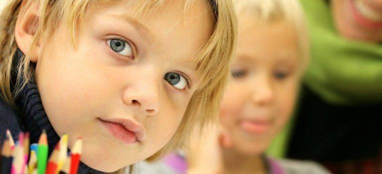 na pierwszym planie jest uśmiechnięta twarz dziecka, przed którym stoją kredki. Na drugim planie widać twarz drugiego dziecka, które robi coś z koncentracją. To ilustracja projektu dostępna szkoła