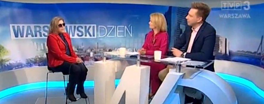 w studiu programu Warszawski dzień, po lewej stronie na stołku siedzi kobieta, w czerwonej marynarce i ciemnych okularach - to Justyna Kucińska, prezeska naszej Fundacji, obok niej leży Pepper. Na środku znajduje się wysoki stół, po jego prawej stronie siedzi dwóch redaktorów prowadzących rozmowę z Justyną - kobieta oraz mężczyzna