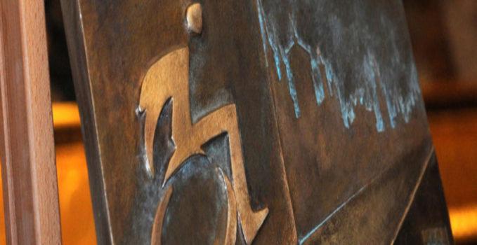 lekki zarys postaci na wózku na miedzianym tle. To wzór nagrody w konkursie Kraków bez barier