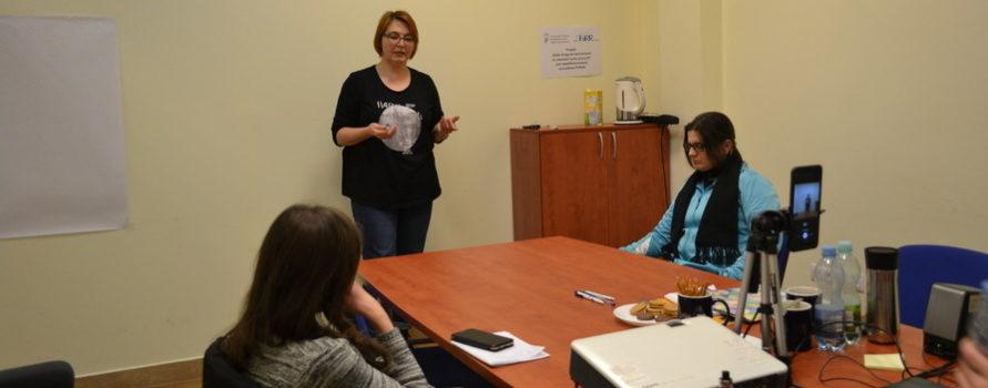 trzy kobiety są w pokoju, jedna w czarnej bluzce stoi i gestykuluje, dwie pozostałe siedzą i słuchają. To uczestniczki projektu stażowego.