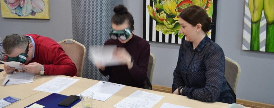 trzy osoby, dwie kobiety i mężczyzna siedzą przy stole. Kobieta jest w symulatorze wady wzroku, również mężczyzna. Trzymają kartki w dłoniach i próbują odczytać tekst. Trzecia kobieta obserwuje ich. To uczestnicy szkolenia Dostępna administracja publiczna, szkolenia dla kadry