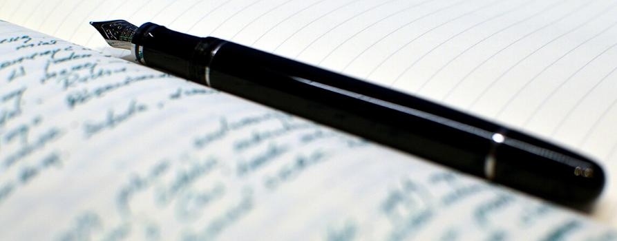 czarne pióro do pisania położone na otwartym zapisanym notatniku