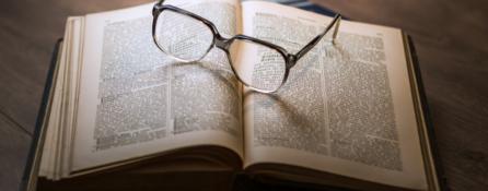 na drewnianym stole leży otwarta książka. na książce leżą okulary.