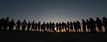 zachód słońca, które jest już prawie przy samym horyzoncie. na tle tego nieba widać kontury około 20 osobowej grupy ludzi, która trzyma się za ręce.
