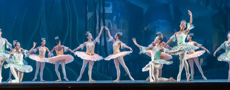 scena teatralna. na tle niebieskiej scenografii tańczy kilkanaście baletnic ubranych w pastelowe stroje.