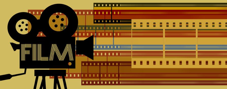 grafika.po lewej stronie czarny projektor z dwiema nawiniętymi na szpule taśmami. na projektorze jest napis FILM. na prawo od projektora graficzne kolorowe paski z taśm filmowych.