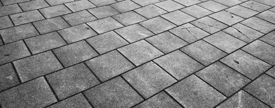 czarno-białe zdjęcie chodnika z kwadratowych betonowych płyt.