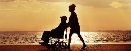 na tle zachodu słońca nad morzem kobieta prowadzi na wózku inwalidzkim mężczyznę.