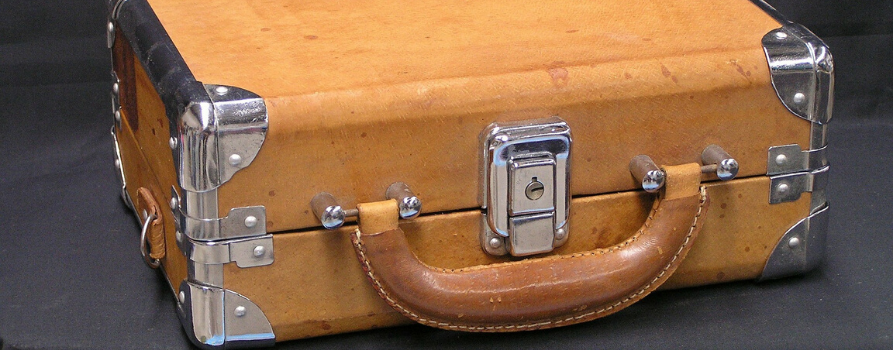 jasna skórzana walizka w stylu retro. walizka posiada metalowe srebrne zamknięcie oraz takie same metalowe okucia na rogach.