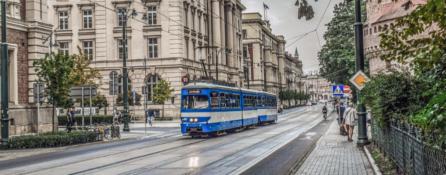 ulica Krakowa. po torach tramwajowych jedzie niebieski tramwaj, po chodniku idą przechodnie.