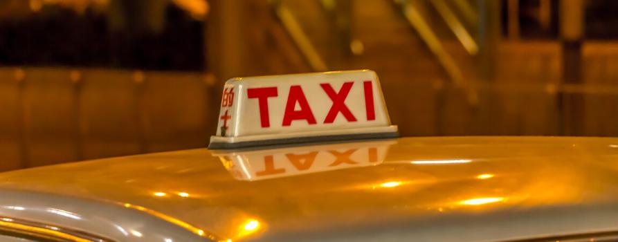 fragment żółtego dachu samochodu z tabliczką z napisem TAXI