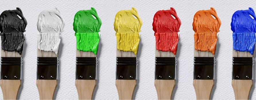 na białej kartce leżą równo ułożone pędzle do malowania. na każdy z nich nabrana jest kolorowa farba.