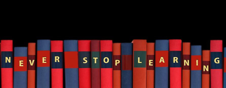 """Na czarnym tle kolorowe grzbiety książek. Na ich grzbietach są białe litery układające się w napis po angielsku """"nigdy nie przestawaj się uczyć"""""""