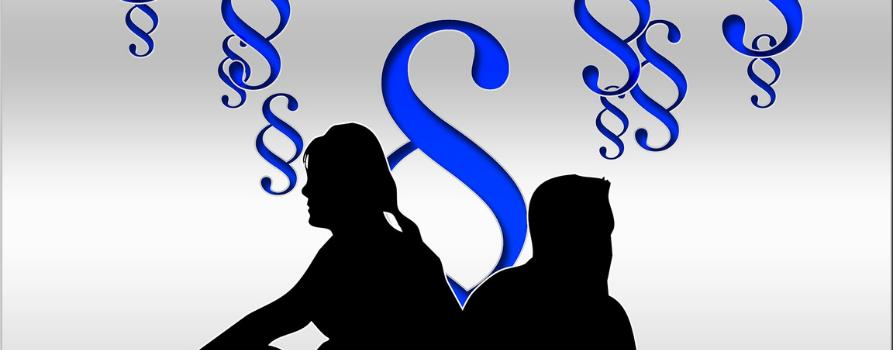 czarne kontury sylwetek siedzących mężczyzny i kobiety na białym tle. nad ich głowami niebieskie znaki paragrafów