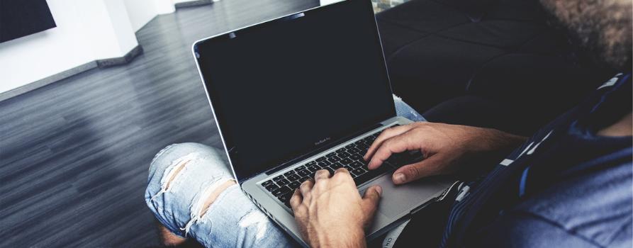 fragment siedzącej sylwetki mężczyzny z laptopami na kolanach