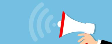 grafika. po prawej stronie na niebieskim tle wyciągnięta dłoń trzyma biało-czerwony megafon