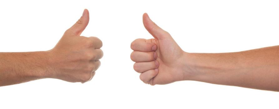 na białym dwie dłonie z uniesionymi kciukami do góry