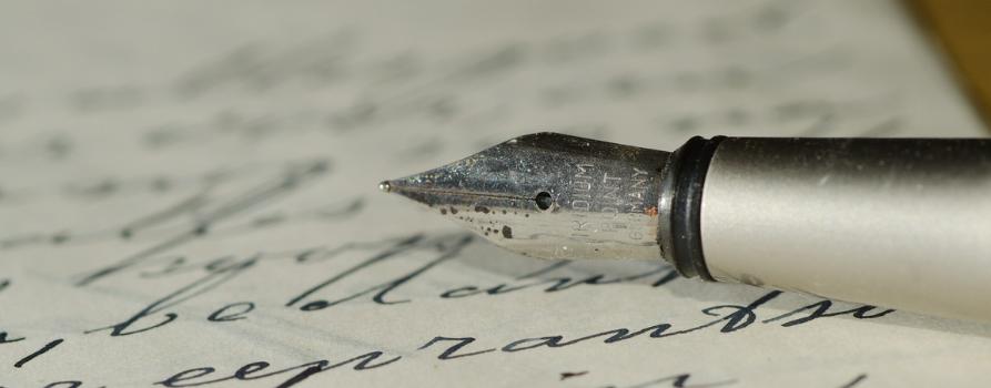 zbliżenie na srebrną stalówkę pióra, które leży na zapisanej kartce