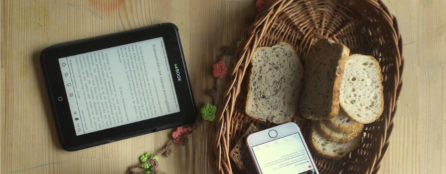 na jasnym blacie stołu po lewej leży czytnik ebooków. obok na prawo wiklinowy koszyk, w którym leży kilka kromek chleba i smartfon