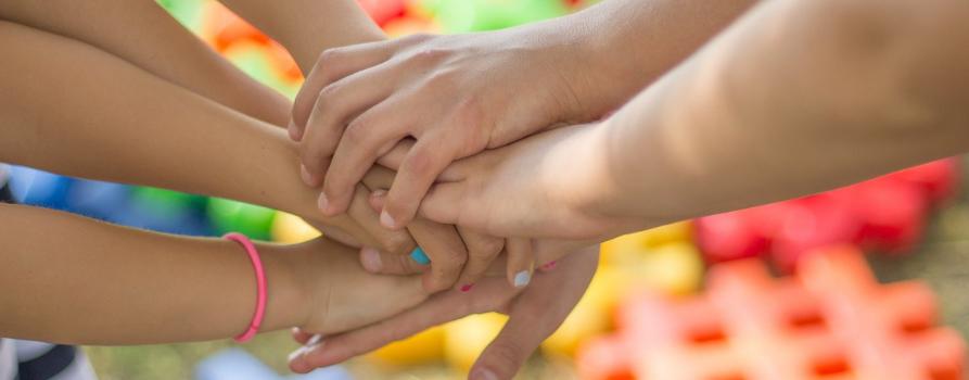 zbliżenie na kilka trzymających się dłoni - jeden za wszystkich, wszyscy za jednego
