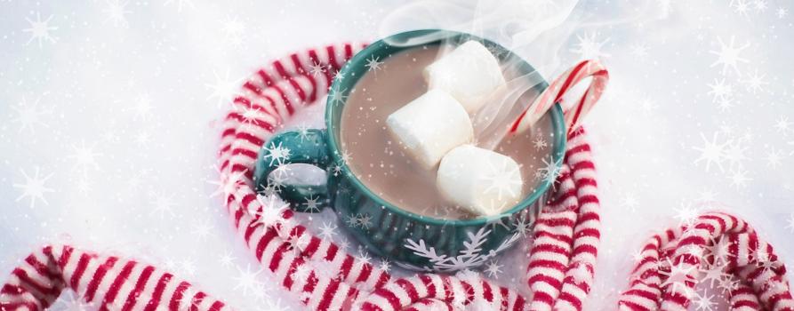 na śniegu stoi niebieski kubek po brzegi wypełniony gorącym kakao, na którym unoszą się białe pianki. a żeby było jeszcze cieplej, kubek jest owinięty szalikiem w biało-czerwone paski