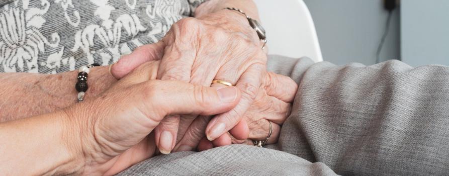 zbliżenie na trzymające się dłonie - jedne należą do osoby starszej, drugie do młodszej