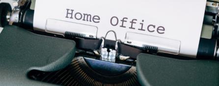 fragment maszyny do pisania, z której wystaje kartka z napisem home office
