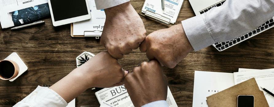 nad biurkiem, na którym leżą dokumenty, tablety, cztery zaciśnięte dłonie, stykające się ze sobę: jeden za wszystkich, wszscy za jednego
