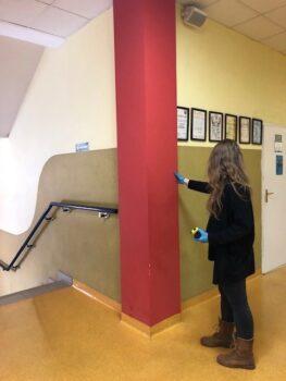 wnętrze budunku, przy ścianie koło schodów stoi kobieta, która dokonuje odpowiednie pomiary
