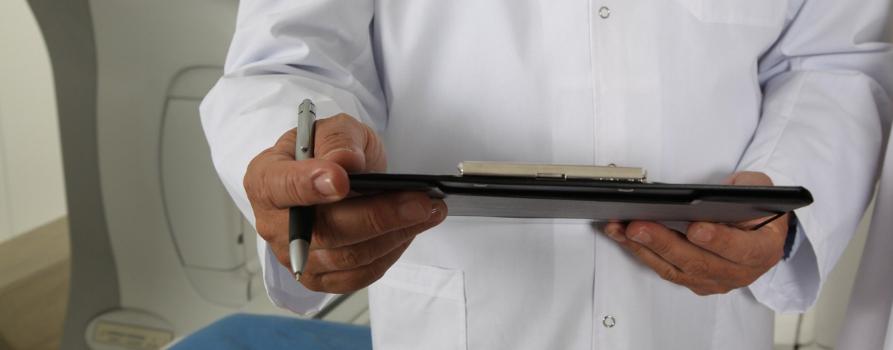 fragment sylwetki lekarza - osoba w białym kitlu trzyma notatnik oraz długopis