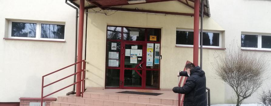 Przy schodach prowadzących do wejścia do budynku stoi pracownik FIRR, wykonując pomiary poręczy.