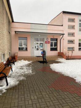 budynek szkoły podstawowej w wilkowie w zimowej scenerii. przed budynkiem pracowniczka FIRR