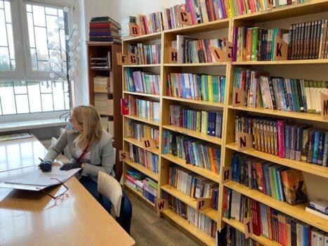 W bibliotece w Przedmościu przy biurku siedzi kobieta, za nią regał uginający się od książek