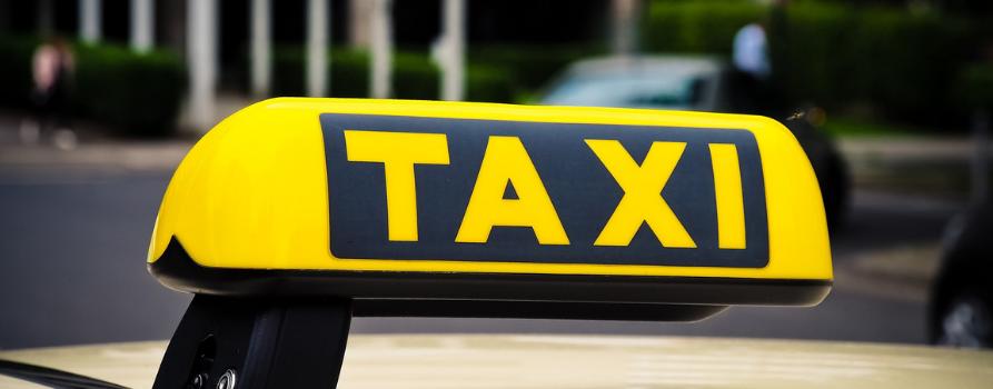 zbliżenie na tabliczkę informacyjną z napisem TAXI na dachu samochodu