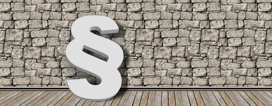 biały trójwymiarowy znak paragrafu stoi oparty o szarą kamienną ścianę.