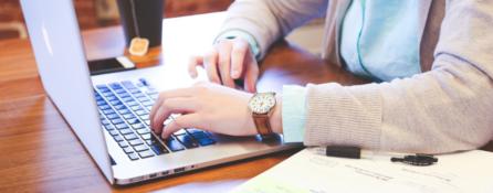 fragment kobiecej sylwetki, która siedzi przy biurku przed laptopem