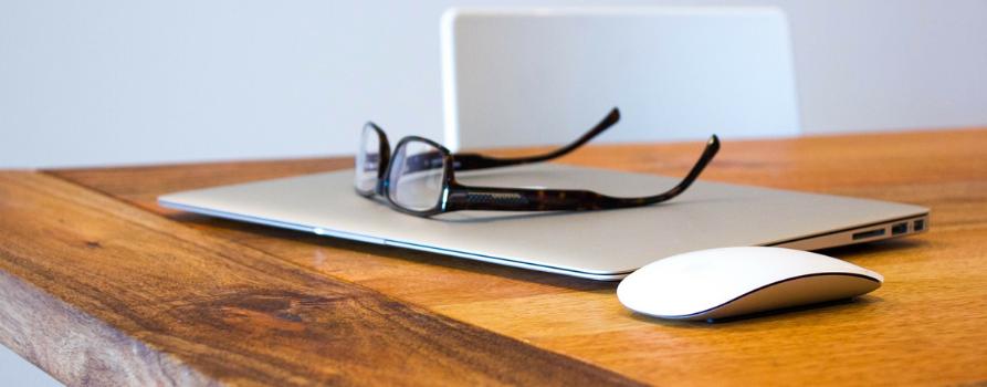 na drewnianym stole leży laptop a na nim okulary, obok tapropa, po prawej stronie myszka.