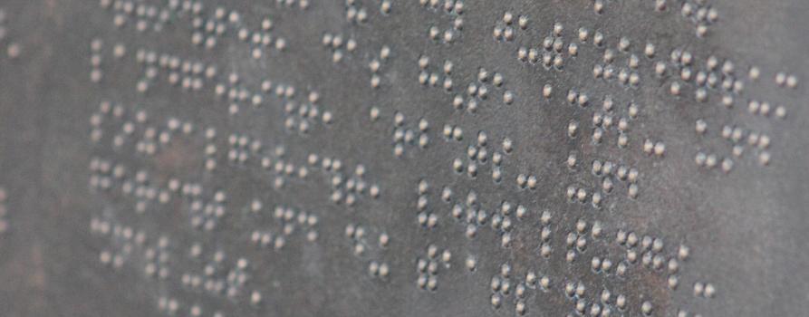 zbliżenie na białą kartkę zapisaną Braille'm