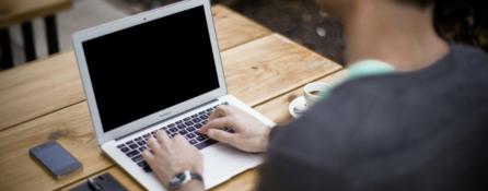 fragment męskiej sylwetki siedzącej przy stole z rękoma na klawiaturze laptopa