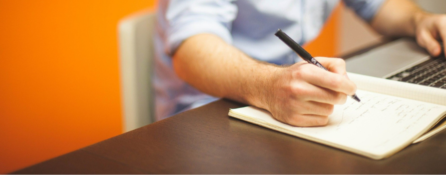 fragment męskiej sylwetki przy biurku. jedną dłoń trzyma na klawiaturze, w drugiej ma długopis i coś notuje na kartce