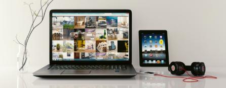 na białym stole od lewej: laptop, tablet oraz słuchawki