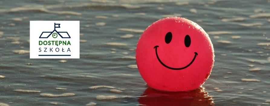 rożowa piłka z namalowanym uśmiechem na powierzchni wody jeziora. po lewej stronie logo dostępnej szkoły