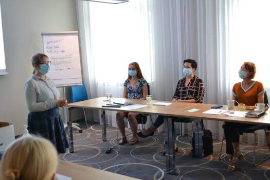 na pierwszym planie trenerka Katarzyna Balwierz, na dalszym przy stole siedzą trzy uczestniczki