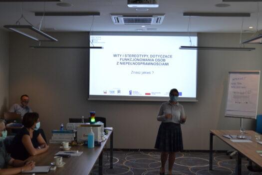 Na tle dużego ekranu z wyświetloną prezentacją stoi trenerka Katarzyna Balwierz