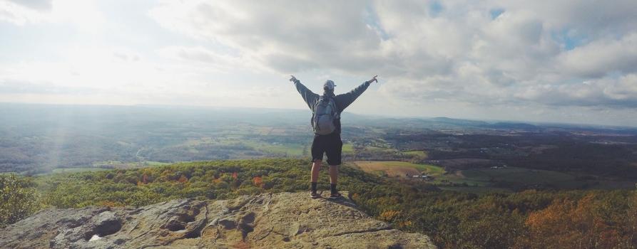 góry. tył mężczyzny stojącego z rozłożonymi rękoma. przed nim rozpościera się ogromna przestrzeń oraz niebieskie niebo usiane białymi obłokami
