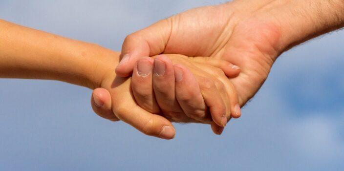 trzymające się dłonie - symbol wsparcia i pomocy