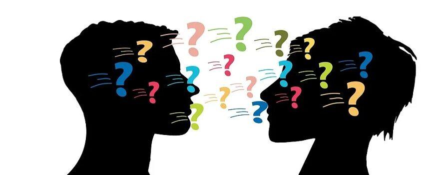 grafika: dwie głowy z profilu, damska i męska, czarne na białym tle.Między nimi kolorowe znaki zapytania