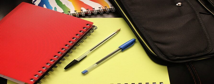 Skoroszyt w kolorze czerwonym po lewej stronie, na środku żółty skoroszyt, na nim dwa długopisy, powyżej skoroszyt w kolorowe wzory. Po prawej stronie obrazka czarny przybornik.